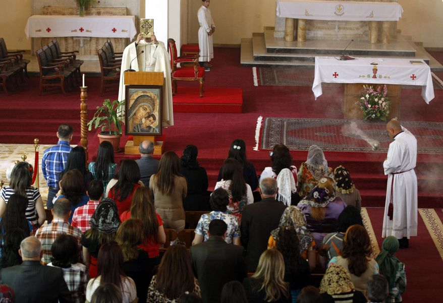 Iraqi Christians pray during Easter Mass at Mar Youssif Chaldean Church in Baghdad on Sunday, March 31, 2013. The Chaldean Church is an Eastern Rite church affiliated with the Roman Catholic Church. (AP Photo/Karim Kadim)