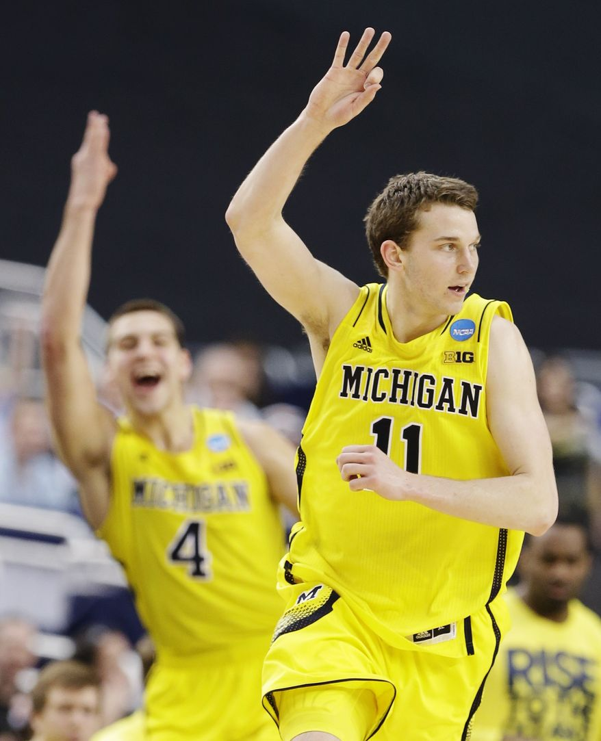Michigan's Nik Stauskas (11) celebrates his three-point basket as Mitch McGary (4) joins in against Florida during the second half of a regional final game in the NCAA college basketball tournament, Sunday, March 31, 2013, in Arlington, Texas. (AP Photo/Tony Gutierrez)