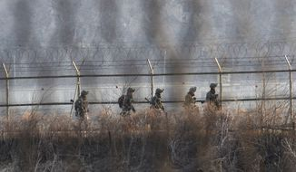 "South Korean soldiers patrol along a barbed-wire fence in Paju, South Korea, near the border village of Panmunjom, on Sunday, March 31, 2013. North Korea warned South Korea on Saturday that the Korean Peninsula had entered ""a state of war"" and threatened to shut down a border factory complex that's the last major symbol of inter-Korean cooperation. (AP Photo/Ahn Young-joon)"