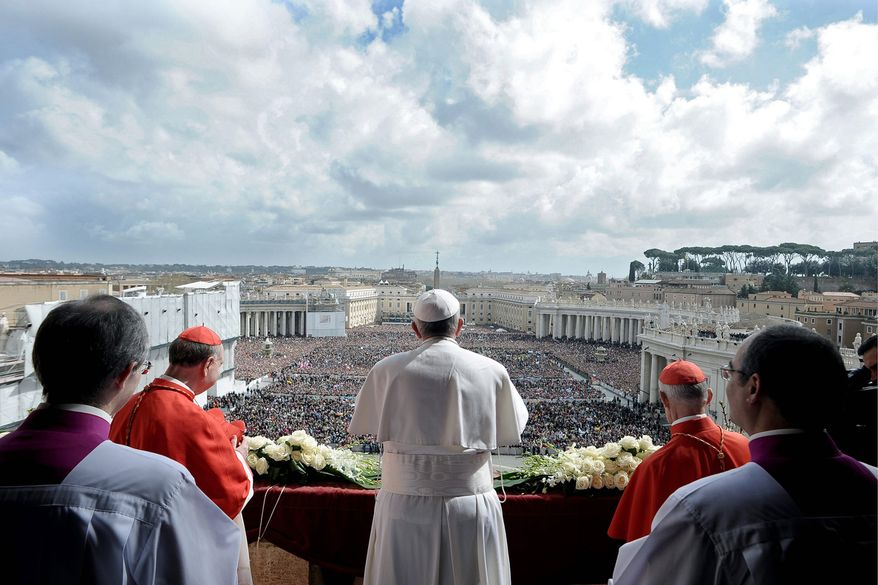 Pope Francis delivers the Urbi et Orbi (to the city and to the world) blessing, in St. Peter's Square at the Vatican on Sunday. Francis celebrated his first Easter Sunday Mass as pontiff before joyous pilgrims, tourists and Romans in the square bedecked by spring flowers. (L'Osservatore Romano via the Associated Press)