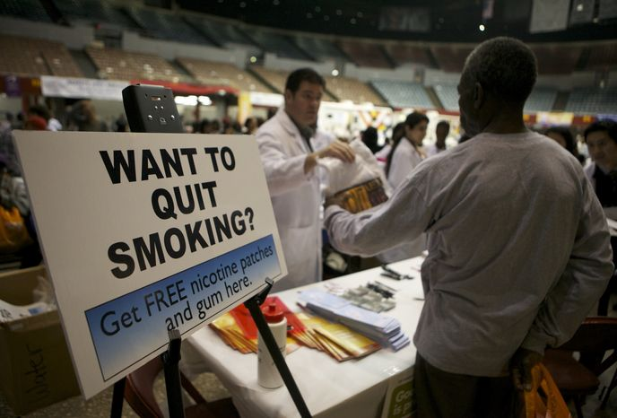 **FILE** Smokers without medical insurance receive free nicotine patches and gum at the Remote Area Medical (RAM) clinic inside the Los Angeles Sports Arena in Los Angeles on April 27, 2010. (Associated Press)