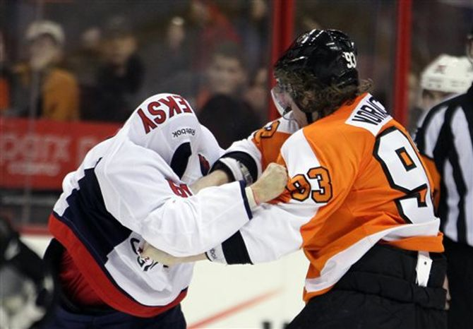 Washington Capital's Steve Oleksy, left, his sweater pulled over his head, fights with Philadelphia Flyers' Jakub Voracek in the third period of an NHL hockey game, Sunday, March 31, 2013, in Philadelphia. Voracek was assessed four penalties including a ten-minute penalty for gross misconduct. The Flyers won 5-4. (AP Photo/Tom Mihalek)