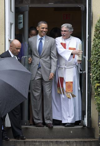 President Barack Obama exits St. John's Episcopal Church with the Rev. Luis Leon after he and the first family attended Easter services, Sunday, March 31, 2013, in Washington. (AP Photo/Carolyn Kaster)