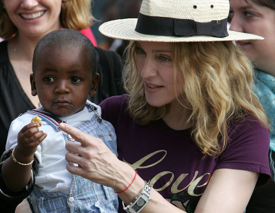 ** FILE ** The American pop singer Madonna carries David Banda, her Malawian adopted son, at Consol Homes, a day care center that she funds in the village of Masekese, Malawi, in 2007. (AP Photo/Karel Prinsloo)