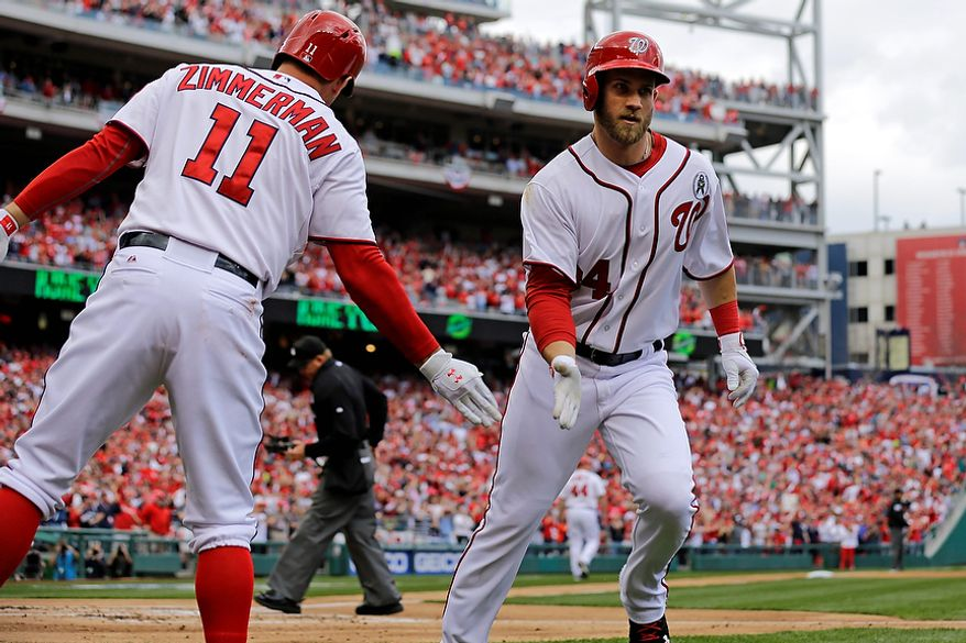 Washington Nationals left fielder Bryce Harper (34) is congratulated by third baseman Ryan Zimmerman (11) after a first inning solo homer during the opening day baseball game against the Miami Marlins in Washington, on Monday, April 1, 2013.  (AP Photo/Alex Brandon)