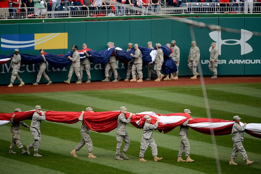 Members of the military carry a large American flag out onto the field as the Washington Nationals play the Miami Marlins on opening day at Nationals Park, Washington, D.C., Monday, April 1, 2013. (Andrew Harnik/The Washington Times)