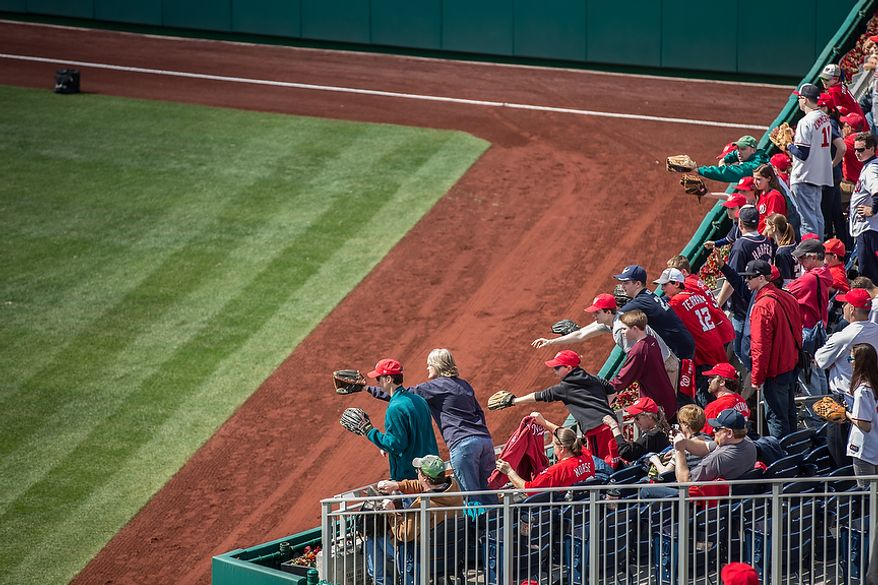 Fans lean over the center field wall to try to catch the attention of their favorite ball players during warm up, as the Washington Nationals play the the Miami Marlins on opening day, at Nationals Park, in Washington, DC., Monday, April 1, 2013. (Andrew S Geraci/The Washington Times)