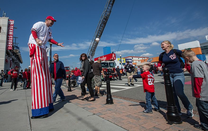 Mark Lohr, a stilt walker, plays catch with a child as they make their way into the ball park to watch the Washington Nationals play the the Miami Marlins on opening day, at Nationals Park, in Washington, DC., Monday, April 1, 2013. (Andrew S Geraci/The Washington Times)