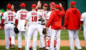 Washington Nationals left fielder Bryce Harper (34), center, celebrate with teammates as the Washington Nationals beat the Miami Marlins 2-0 on opening day at Nationals Park, Washington, D.C., Monday, April 1, 2013. (Andrew Harnik/The Washington Times)