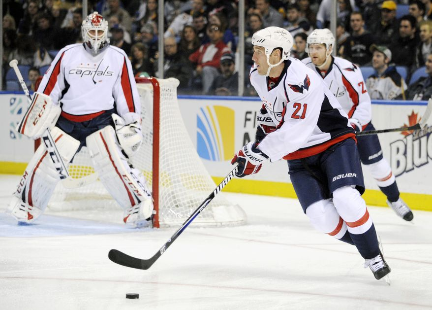 Washington Capitals' center Brooks Laich (21) carries the puck up ice against the Buffalo Sabres during the first period of an NHL hockey game in Buffalo, N.Y., Saturday, March 30, 2013. (AP Photo/Gary Wiepert)