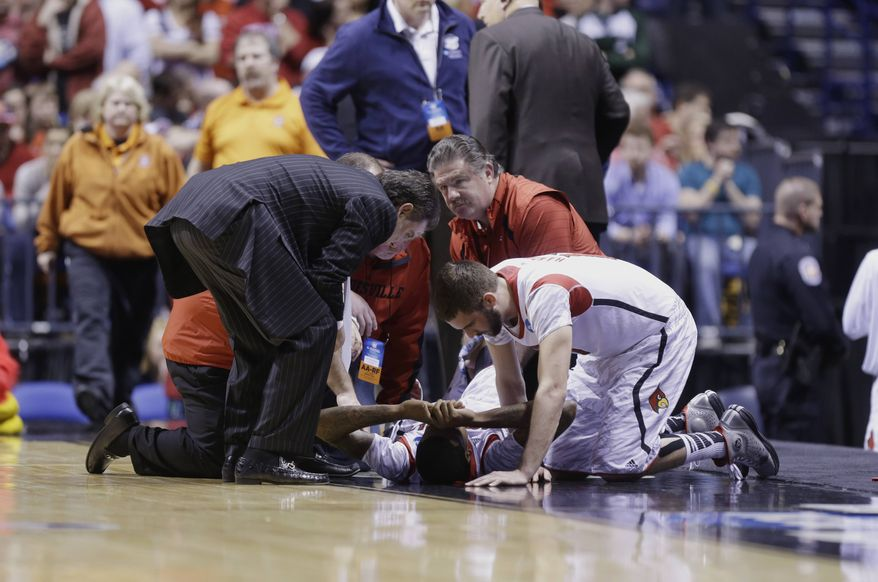 Louisville head coach Rick Pitino, left, and Louisville's Stephan Van Treese, right, talk to injured guard Kevin Ware as trainers tend to Ware during the first half of the Midwest Regional final against Duke in the NCAA college basketball tournament, Sunday, March 31, 2013, in Indianapolis. (AP Photo/Michael Conroy)