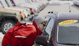 Matthew Miller of Omaha, Neb., shops for a car on Thursday, March 14, 2013. (AP Photo/Nati Harnik)