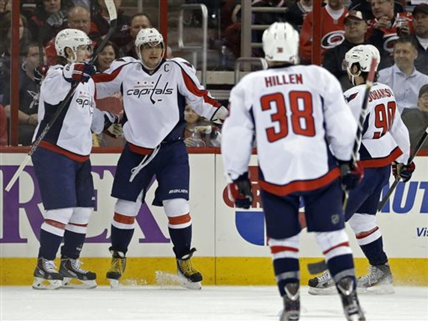 Washington Capitals' Alex Ovechkin (8), of Russia, and Nicklas Backstrom, left, of Sweden, celebrate Ovechkin's goal against the Carolina Hurricanes with Jack Hillen (38) and Marcus Johansson (90), of Sweden, during the second period of an NHL hockey game in Raleigh, N.C., Tuesday, April 2, 2013. (AP Photo/Gerry Broome)