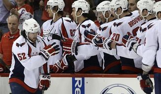 Washington Capitals' Mike Green (52) celebrates his goal against the Carolina Hurricanes with teammates on the bench during the second period of an NHL hockey game in Raleigh, N.C., Tuesday, April 2, 2013. (AP Photo/Gerry Broome)