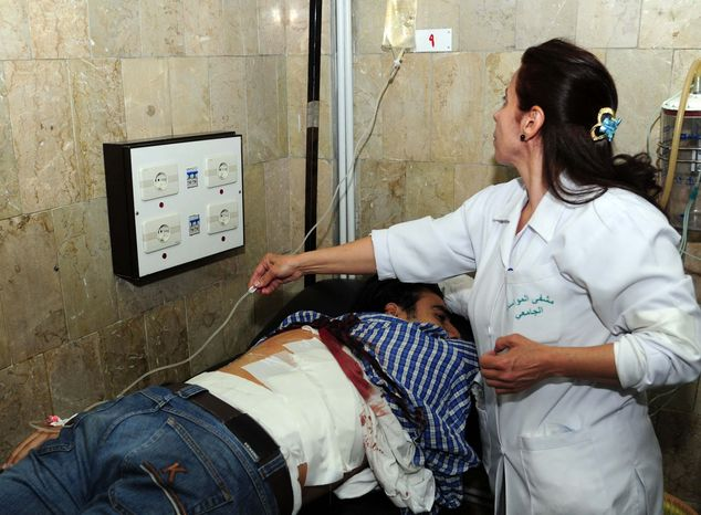** FILE ** In this Thursday, March 28, 2013, photo released by the Syrian official news agency SANA, a Syrian doctor treats an injured man who was wounded at the open-air cafeteria at Damascus University in the central Baramkeh district, in Damascus, Syria. More than 6,000 people were killed in the Syrian civil war in March alone, according to a leading activist group that reported it was the deadliest month yet in the 2-year-old conflict. (AP Photo/SANA, File)