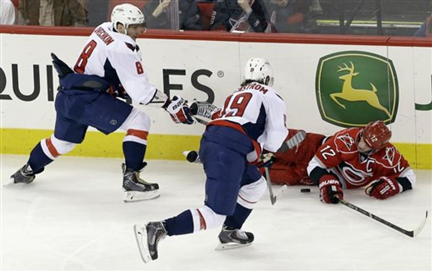 Carolina Hurricanes' Eric Staal (12) falls to the ice chasing the puck against Washington Capitals' Alex Ovechkin (8), of Russia, and Nicklas Backstrom (19), of Sweden, during the third period of an NHL hockey game in Raleigh, N.C., Tuesday, April 2, 2013. Washington won 5-3. (AP Photo/Gerry Broome)