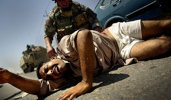 August 16, 2006: CPL David Stigers from Bravo Company, 2nd Battalion, 6th Infantry Regiment, 1st Armored Division, Baumholder, GE, administers first aid to an injured Iraqi man that was shot. U.S. Forces came under fire from Anti Iraqi Forces during a Traffic Control Point (TCP) on Alternate Supply Route Michigan in Tameem, Ramadi, Iraq.  TCP's are performed by pulling over random vehicles, searching the vehicle and it's occupants for weapons or explosives being transported into the city.  (U.S. Air Force photo by Tech. Sgt. Jeremy T. Lock)