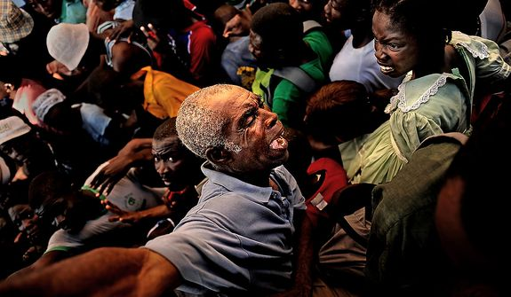 An older man is squished while he tries to get out of the way of a huge number of Haitians making their way to the relief supplies (food and water) the U.S. Army Soldiers with Charlie Company, 2nd Battalion, 325th Airborne Infantry Regiment, 2nd Brigade Combat Team, 82nd Airborne Division, Fort Bragg, NC,were handing out on January 20, 2010 at the stadium in Port au Prince, Haiti, for Operation Unified Response. As more and more Haitians heard of the distribution being handed out by the soldiers, the distribution line turned into a huge gathering of people being pushed from the back. The soldiers stood their ground and handed out the majority of the relief for as long as they could before they were hugely out numbered and over run.  (U.S. Air Force photo by Tech. Sgt. Jeremy T. Lock)