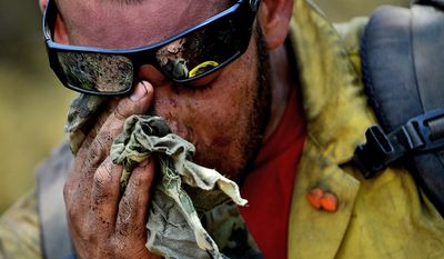 Vandenberg Air Force Base Hot Shot fire fighter Chris Loung wipes sweat from his face while cutting a fire line on June 28, 2012 in the Mount Saint Francois area of Colorado Springs, Co. while helping to battle several fires in Waldo Canyon.   (U.S. Air Force photo by Tech. Sgt. Jeremy T. Lock)