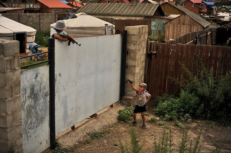 Two young boys run around and play with toy guns in the Ger District in Ulaanbaatar, Mongolia on July 28, 2012. Ger districts usually occupy poor quality land on the outskirts of town.  (U.S. Air Force photo by Tech. Sgt. Jeremy T. Lock)