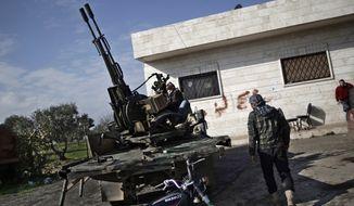 ** FILE ** In this Friday, Dec. 14, 2012, file photo, a Syrian rebel checks an anti-aircraft weapon, in Maaret Misreen, near Idlib, Syria. (AP Photo/Muhammed Muheisen, File)