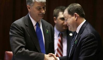 Senate Minority Leader John McKinney, R-Fairfield, who represents Newtown, Conn., right, and Senate President Donald Williams, D-Brooklyn, shake hands after the passage of a gun-control bill in the Senate chamber at the Capitol in Hartford, Conn., Wednesday, April 3, 2013. (AP Photo/Charles Krupa)