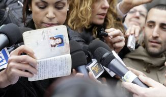 Karima el-Mahroug, also known as Ruby, left, a Moroccan woman at the center of ex-Premier Silvio Berlusconi's sex-for-hire trial, holds up her passport as she is surrounded by reporters outside Milan's court house, Italy, Thursday, April 4, 2013. (AP Photo/Luca Bruno)