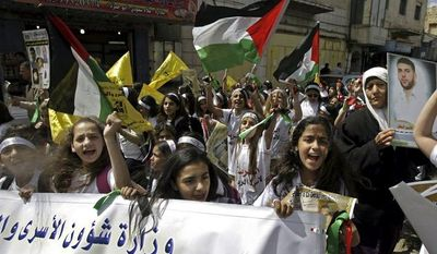 Palestinian students chant slogans during a protest in the West Bank city of Jenin on Thursday, April 4, 2013, after 64-year-old Maysara Abu Hamdiyeh, who was serving a life sentence for a 2002 foiled bombing of a busy Jerusalem cafe, died of cancer in an Israeli prison. (AP Photo/Mohammed Ballas)
