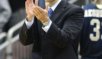 In this Dec. 19, 2012 file photo, Florida International coach Richard Pitino applauds his team's effort during the second half of an NCAA college basketball game against Louisville in Louisville, Ky.  Pitino is now the coach at Minnesota. (AP Photo/Timothy D. Easley, File)