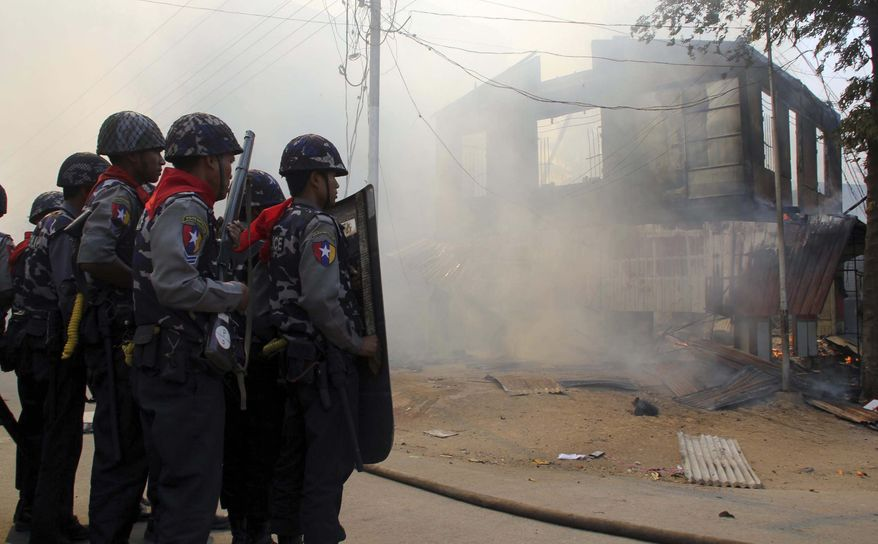 ** FILE ** In this Thursday, March 21, 2013 file photo, armed Myanmar police officers provide security around a smoldering building following ethnic unrest between Buddhists and Muslims in Meikhtila, Mandalay division, about 550 kilometers (340 miles) north of Yangon, Myanmar. (AP File Photo)