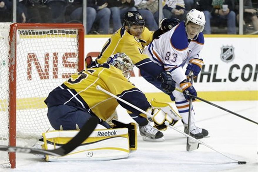 Nashville Predators goalie Pekka Rinne (35), of Finland, blocks a shot as left wing Martin Erat (10), of the Czech Republic, and Edmonton Oilers right wing Ales Hemsky (83), of the Czech Republic, chase after the rebound in the first period of an NHL hockey game on Monday, March 25, 2013, in Nashville, Tenn. (AP Photo/Mark Humphrey)