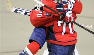 Washington Capitals defenseman John Carlson (74) leaps in the arms goalie Braden Holtby (70) after they won 2-1 against the New York Islanders after overtime and a shootout in an NHL hockey game on Thursday, April 4, 2013, in Washington. (AP Photo/Nick Wass)