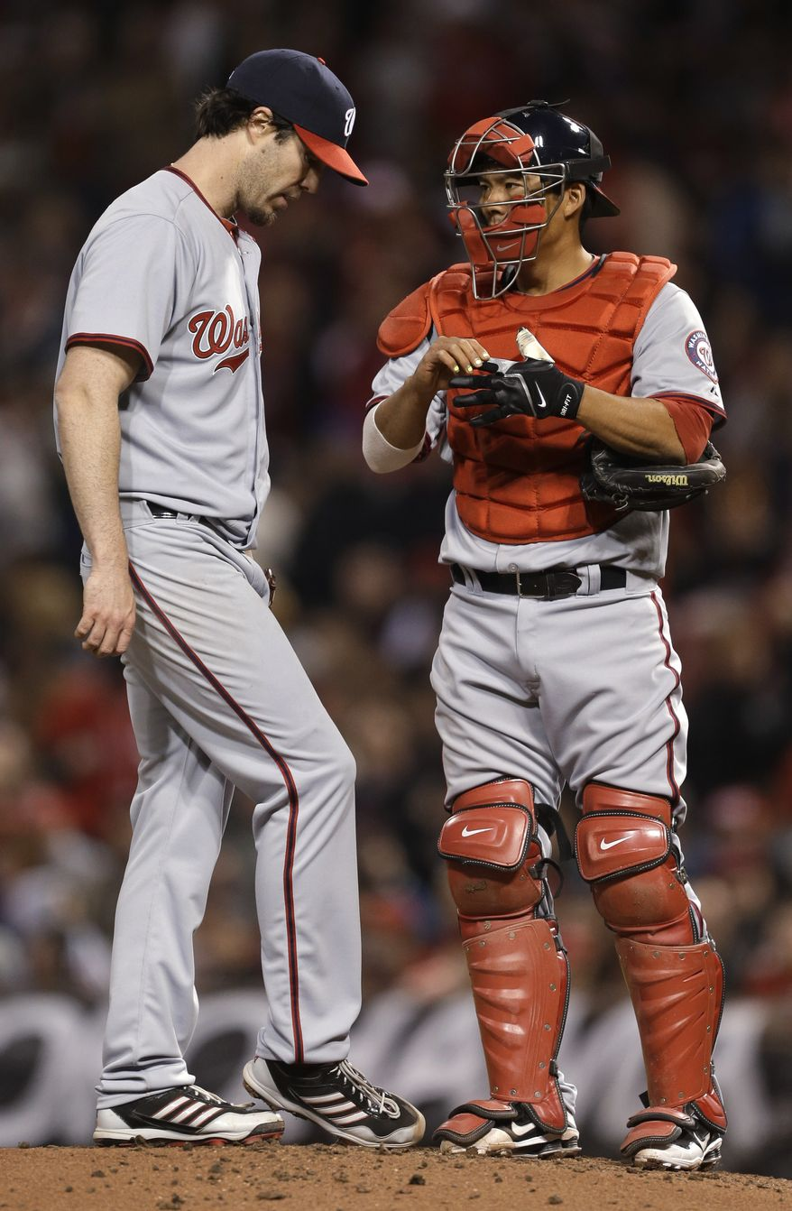 Washington Nationals' right-hander Dan Haren, left, chats with catcher Kurt Suzuki before he is pulled from his regular-season debut. Haren allowed four home runs in four innings and the Nationals gave up six home runs total in a 15-0 loss to the Cincinnati Reds. (Associated Press photo)