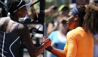 Serena Williams, right, shakes hands with her sister Venus Williams, left, after their semifinal match at the Family Circle Cup tennis tournament in Charleston, S.C., Saturday, April 6, 2013. Serena won 6-1, 6-2. (AP Photo/Stephen Morton)