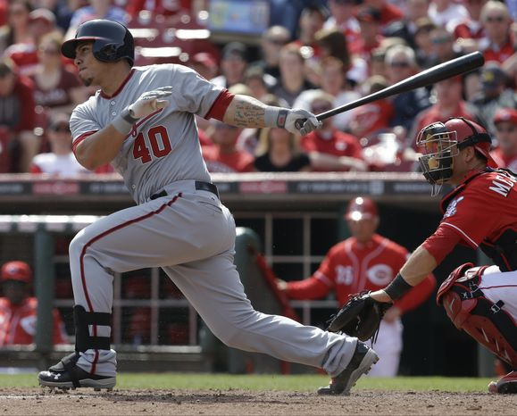 Wilson Ramos follows through on the first of his two home runs in the Washington Nationals' 7-6 victory over the Cincinnati Reds in 11 innings Saturday. Ramos and Ian Desmond hit home runs in the 11th inning to win the game for the Nationals after the Reds tied it at 5-5 in the ninth. (Associated Press photo)