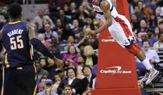 Washington Wizards guard John Wall (2) goes up for a dunk as Indiana Pacers center Roy Hibbert (55) looks on during the first half of an NBA basketball game, Saturday, April 6, 2013, in Washington. (AP Photo/Nick Wass)