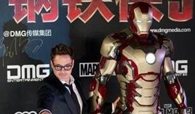 "U.S. actor Robert Downey Jr. poses with a Iron Man figure on stage during a promotional event of his new movie ""Iron Man 3"" before its release in China in early May at the Imperial Ancestral Temple in Beijing's Forbidden City Saturday, April 6, 2013. (AP Photo/Andy Wong)"