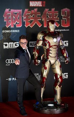 """U.S. actor Robert Downey Jr. poses with a Iron Man figure on stage during a promotional event of his new movie """"Iron Man 3"""" before its release in China in early May at the Imperial Ancestral Temple in Beijing's Forbidden City Saturday, April 6, 2013. (AP Photo/Andy Wong)"""