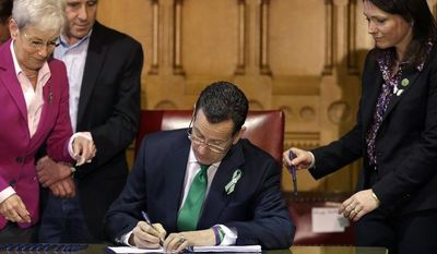 Connecticut Gov. Dannel P. Malloy (center) signs legislation at the Capitol in Hartford, Conn., on Thursday, April 4, 2013, to place new restrictions on weapons and large-capacity ammunition magazines, a response to last year's deadly school shooting in Newtown, Conn. Neil Heslin (behind left), father of Sandy Hook shooting victim Jesse Lewis; Nicole Hockley (right), mother of Sandy Hook School shooting victim Dylan Hockley; and Lt. Gov. Nancy Wyman (left) look on. (AP Photo/Steven Senne)