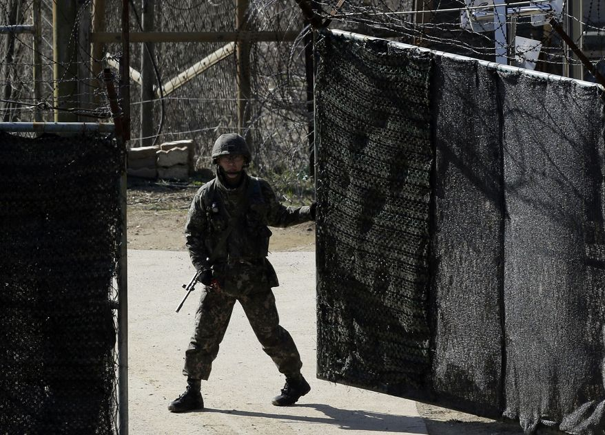 A South Korean soldier closes a military gate in Paju, north of Seoul, on Sunday, April 7, 2013. A top South Korean national security official said Sunday that North Korea may be setting the stage for a missile test or another provocative act with its warning that it soon will be unable to guarantee diplomats' safety in Pyongyang. But he added that the North's clearest objective is to extract concessions from Washington and Seoul. (AP Photo/Lee Jin-man)