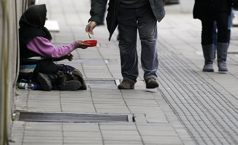 **FILE** A beggar asks for donations in a street in Belgrade, Serbia, on March 7, 2013. There are fears in Serbia that the troubled Balkan nation's economic recovery may slow down because of global financial crisis and rising poverty. (Associated Press)