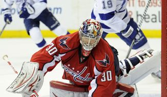 Washington Capitals goalie Michal Neuvirth (30), of the Czech Republic, tracks the puck as Tampa Bay Lightning right wing B.J. Crombeen (19) looks on during the second period of an NHL hockey game, Sunday, April 7, 2013, in Washington. The Capitals won 4-2. (AP Photo/Nick Wass)