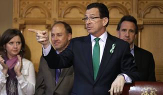 ** FILE ** Connecticut Gov. Dannel P. Malloy (second from right) gestures at the conclusion of a legislation signing ceremony as Jackie and Mark Barden (left and second from left, respectively), parents of Sandy Hook shooting victim Daniel Barden, and Neil Heslin (right), father of Sandy Hook shooting victim Jesse Lewis, look on at the Capitol in Hartford, Conn., on Thursday, April 4, 2013. (AP Photo/Steven Senne)