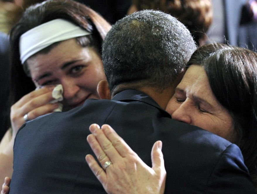 **FILE** President Obama hugs Newtown, Conn., family members after speaking at the University of Hartford in Hartford, Conn., on April 8, 2013. Obama said that lawmakers have an obligation to the children killed and other victims of gun violence to act on his proposals. (Associated Press)