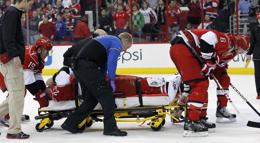 This April 2, 2013 photo shows Carolina Hurricanes hockey player Joni Pitkanen (25), of Finland, being taken off the ice on a stretcher with help from teammates Jiri Tlusty (19), far left, and and Tim Gleason (6), right, during the second period of an NHL game against the Washington Capitals in Raleigh, N.C. The Hurricanes say Pitkanen will miss the rest of the season with a broken heel. General manager Jim Rutherford disclosed the severity of Pitkanen's injury Wednesday, April 3, 2013. (AP Photo/The News & Observer, Chris Seward)