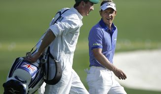 Luke Donald, of England, walks to the driving range with his caddie John McLaren during a practice round for the Masters golf tournament Tuesday, April 9, 2013, in Augusta, Ga. (AP Photo/Matt Slocum)