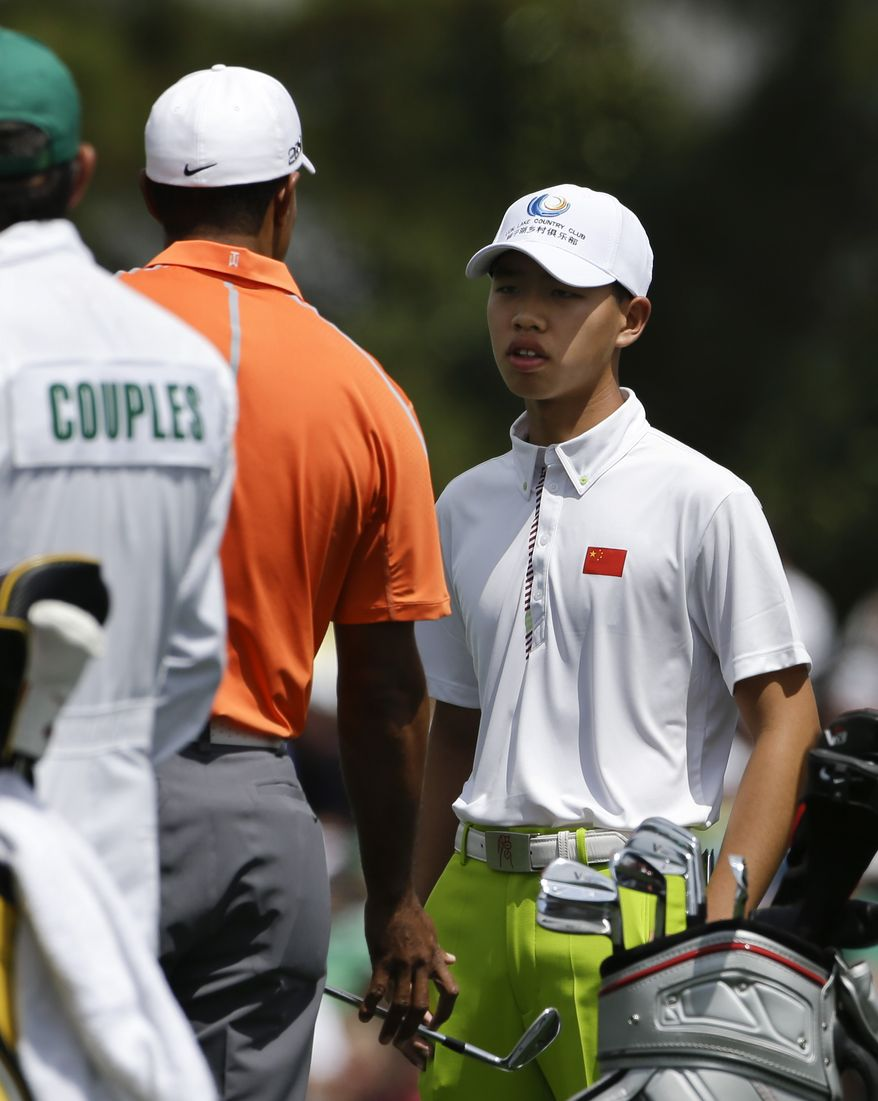 Tiger Woods, left, chats with amateur Tianlang Guan, of China, on the driving range during a practice round for the Masters golf tournament Monday, April 8, 2013, in Augusta, Ga. (AP Photo/Darron Cummings)