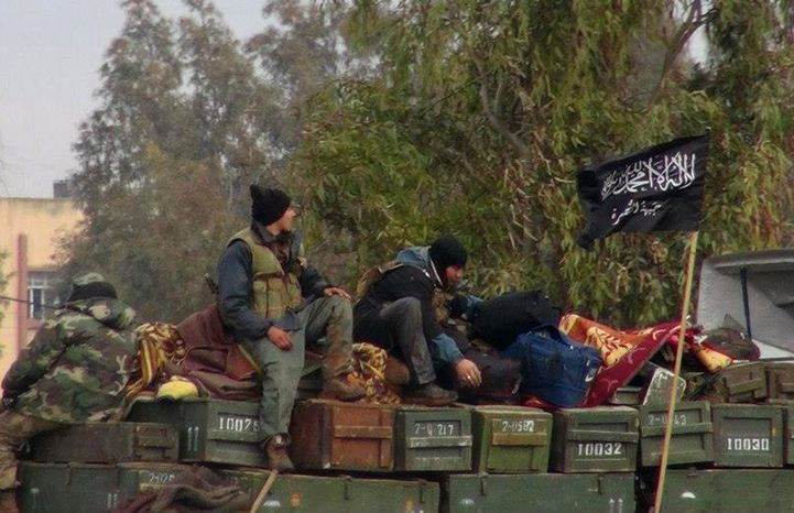 **FILE** In this citizen journalism image provided by Edlib News Network and authenticated based on its contents and other AP reporting, rebels from al Qaeda-affiliated Jabhat al-Nusra sit on a truck full of ammunition at Taftanaz air base, which was captured by the rebels, in the Idlib province of northern Syria. (Associated Press/Edlib News Network)