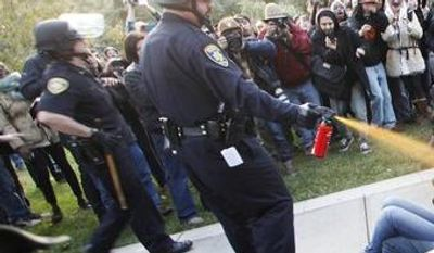 **FILE** University of California, Davis Police Lt. John Pike uses pepper spray to move Occupy UC Davis protesters while blocking their exit from the school's quad in Davis, Calif., on Nov. 18, 2011. (Associated Press/The Enterprise)