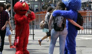 An Elmo character (left) uses a woman's camera to photographer her with a Cookie Monster character in New York's Times Square on April 9, 2013. A string of arrests in the last few months has brought unwelcome attention to the growing number of people, mostly poor immigrants, who make a living by donning character outfits, roaming Times Square and charging tourists a few dollars to pose with them in photos. (Associated Press)
